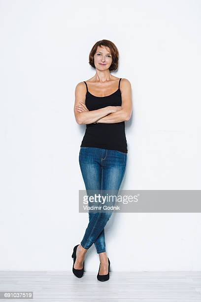 full length portrait of confident woman standing arms crossed against white background - ganzkörperansicht stock-fotos und bilder