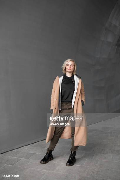 Full length portrait of confident woman standing near gray wall