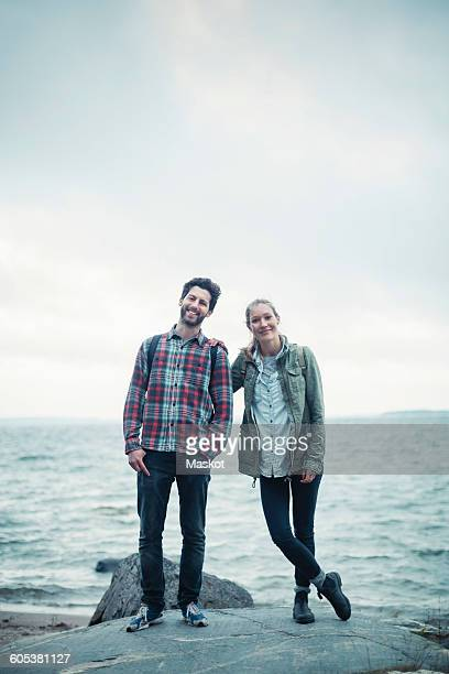 Full length portrait of confident wonderlust couple standing on rock by sea