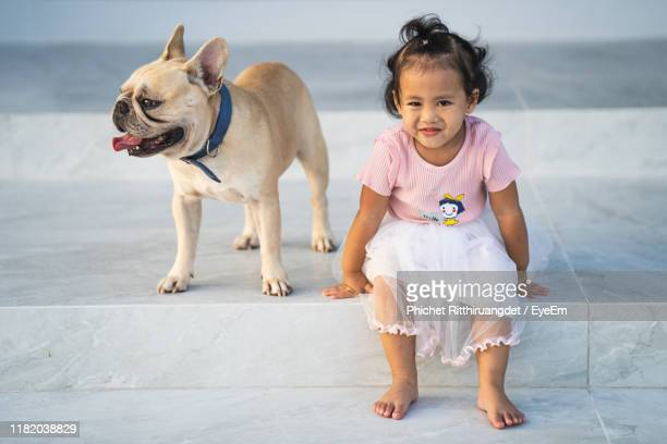 full length portrait of cute girl sitting by dog - phichet ritthiruangdet stock photos and pictures