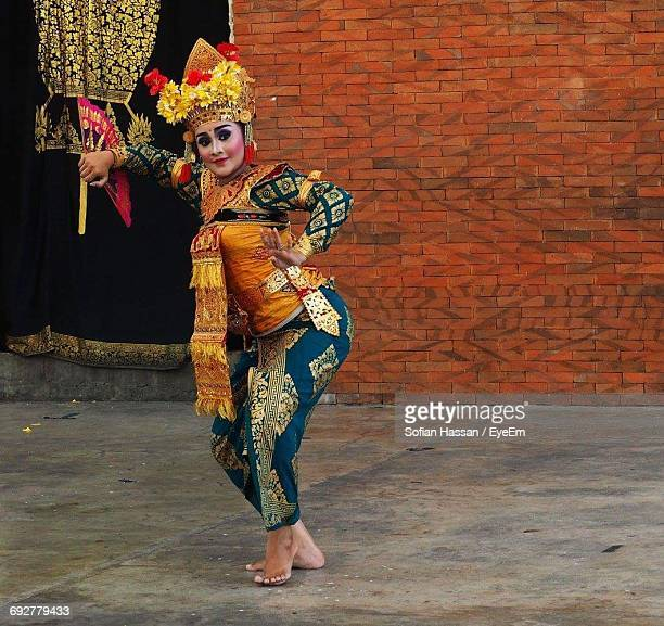 full length portrait of dancer in traditional costume standing against brick wall - balinese culture stock pictures, royalty-free photos & images