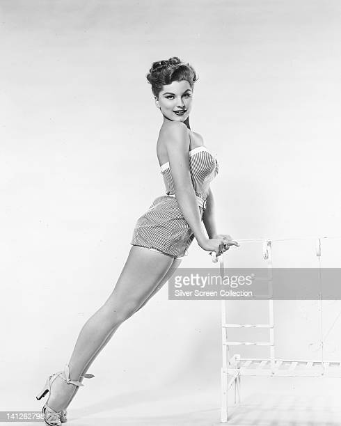 Full length portrait of Debra Paget US actress wearing a striped swimsuit leaning against the back rest of a chair in a studio portrait against a...