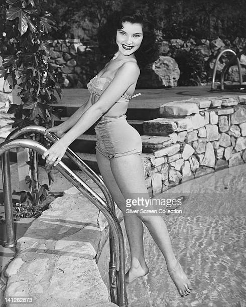 Full length portrait of Debra Paget US actress wearing a swimsuit smiling as she stands on a pool ladder at the edge of a swimming pool circa 1955