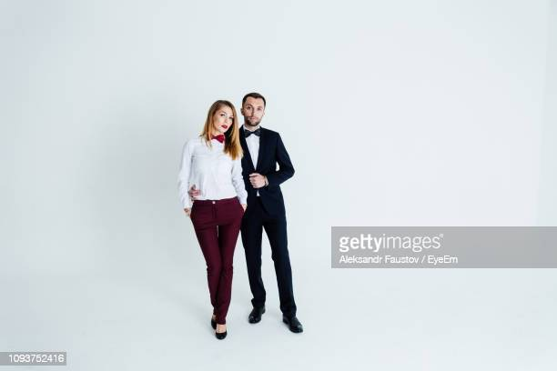 full length portrait of elegant couple standing against blue background - evening wear stock pictures, royalty-free photos & images