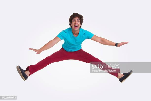 full length portrait of excited young man jumping over white background - legs apart stock pictures, royalty-free photos & images