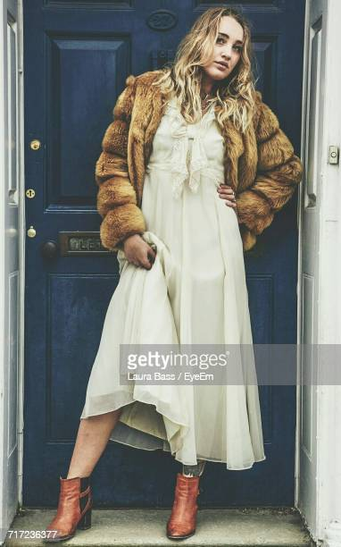 full length portrait of fashionable young woman standing against closed door - fur jacket stock pictures, royalty-free photos & images