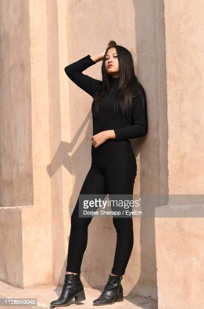 full length portrait of fashionable young woman standing against wall - long sleeved stock pictures, royalty-free photos & images