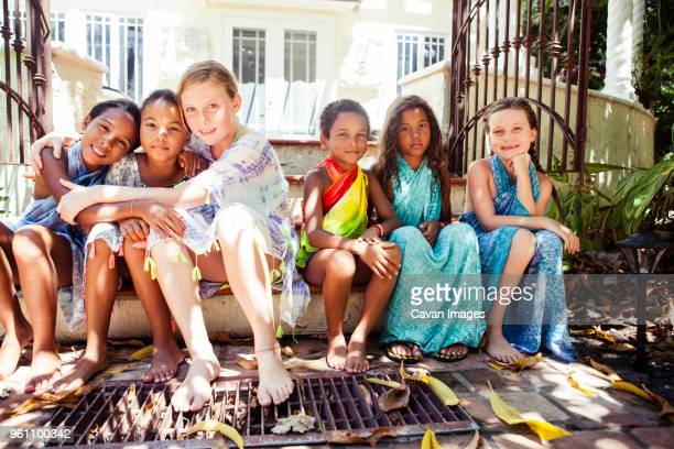 full length portrait of female friends sitting side by side on steps against house - multiculturalism stock pictures, royalty-free photos & images