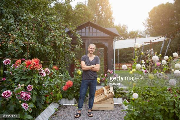 full length portrait of gardener standing arms crossed in yard - green fingers stock pictures, royalty-free photos & images
