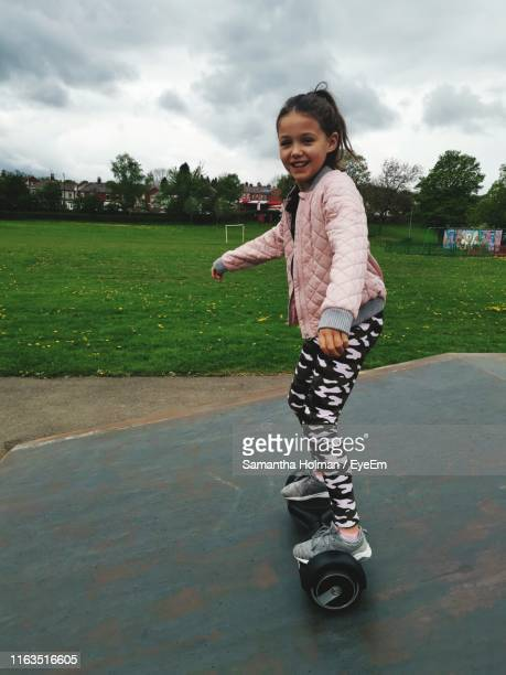 full length portrait of girl hoverboarding at park - hoverboard stock pictures, royalty-free photos & images