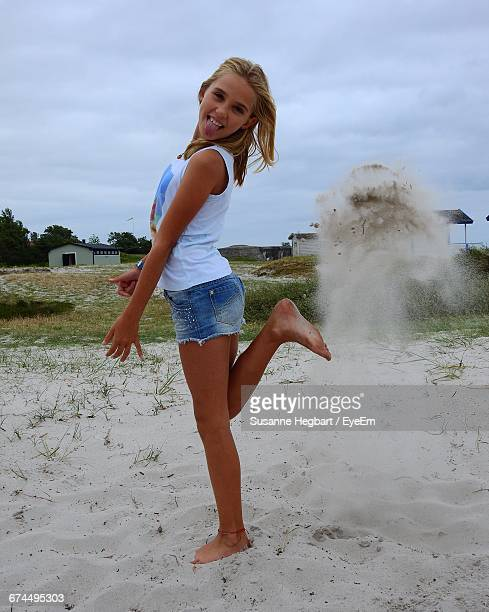 full length portrait of girl playing with sand at beach against sky - hot pants stock photos and pictures