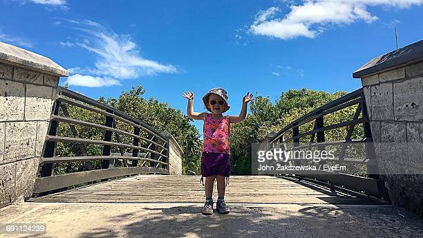 Full Length Portrait Of Girl Standing On Footbridge Against Sky