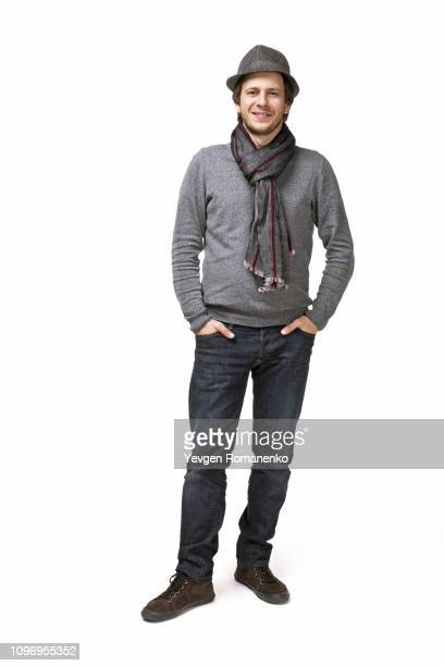 full length portrait of handsome young man in a sweater isolated on white background - men bulges stock photos and pictures