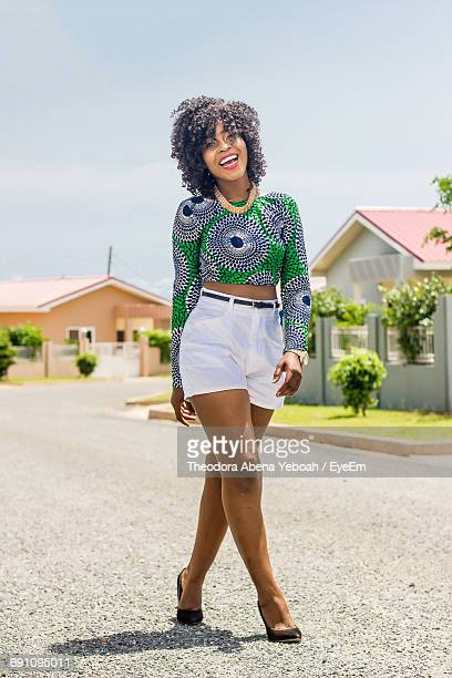 full length portrait of happy beautiful woman walking on road by house against sky - ghana africa fotografías e imágenes de stock