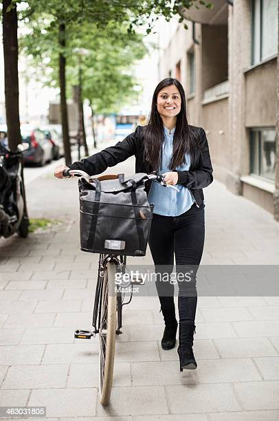 full length portrait of happy businesswoman with bicycle walking on sidewalk - full frontal woman fotografías e imágenes de stock