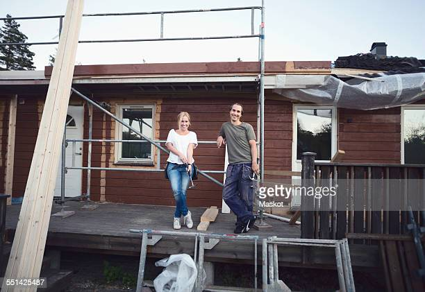 Full length portrait of happy couple leaning on scaffolding of house being renovated