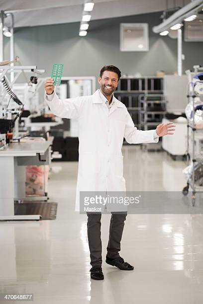 Full length portrait of happy engineer showing machine part in manufacturing industry