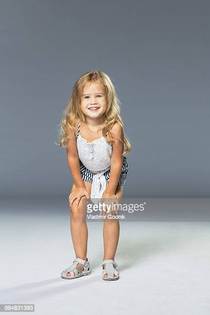 Full length portrait of happy girl standing with hands on knees against gray wall