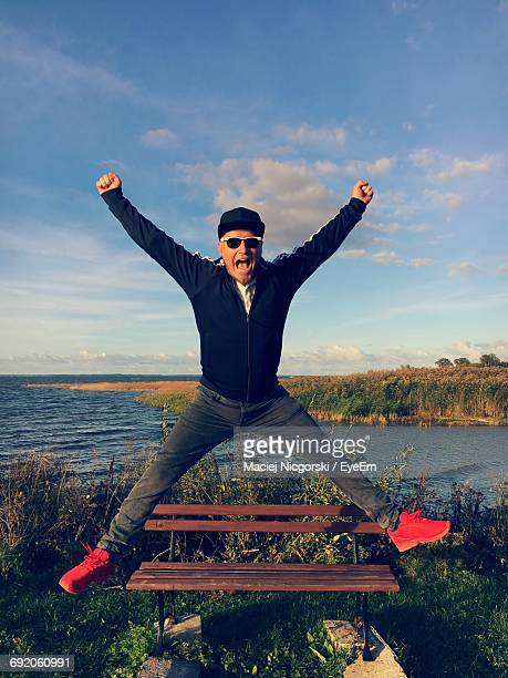 Full Length Portrait Of Happy Man Jumping Against Lake