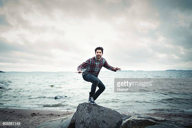 Full length portrait of happy man on rock by sea against cloudy sky