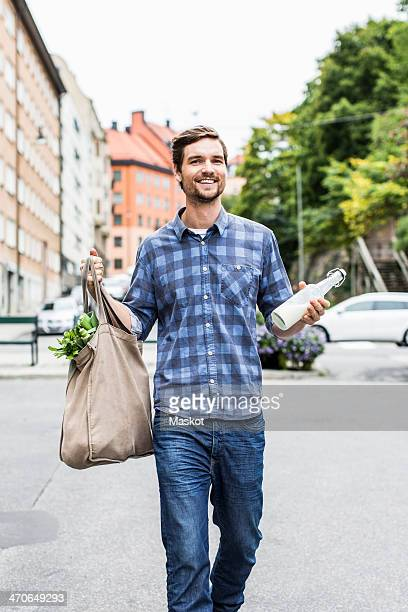Full length portrait of happy man with groceries walking on street