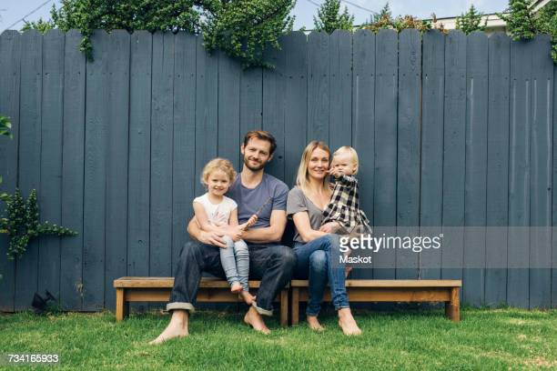 full length portrait of happy parents and children sitting on seats against fence at yard - family with two children stock photos and pictures