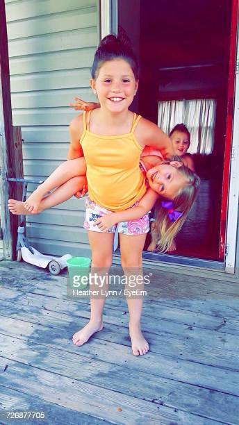 full length portrait of happy playful girl with sister at porch - lynn pleasant photos et images de collection