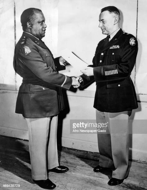 Full length portrait of Howard D Queen from New York being congratulated by Brigadier General William S Howard at the Electrical School at Fort...