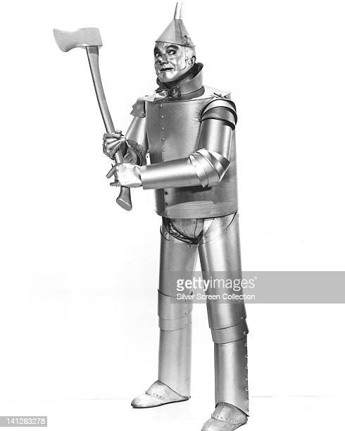 Full length portrait of Jack Haley US actor in costume holding an axe in a studio portrait against a white background issued as publicity from the...