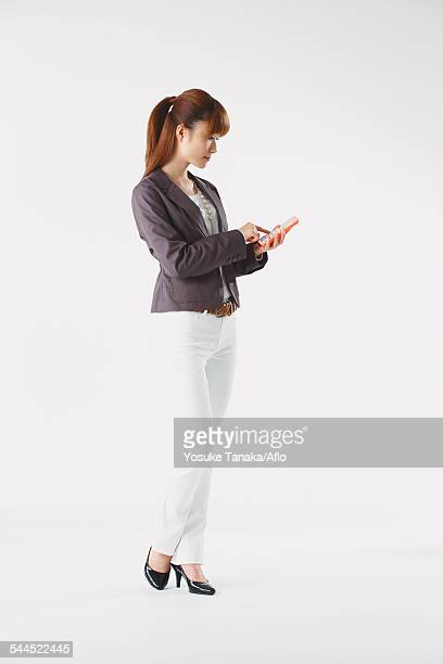 full length portrait of japanese young businesswoman against white background - pump dress shoe stock pictures, royalty-free photos & images