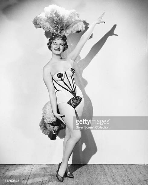 Full length portrait of Joan Sims British actress wearing a showgirl costume with a feather headdress in a studio portrait against a white background...