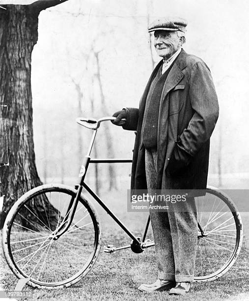 Full length portrait of John D Rockefeller standing next to a chainless shaftdrive bicycle 1913