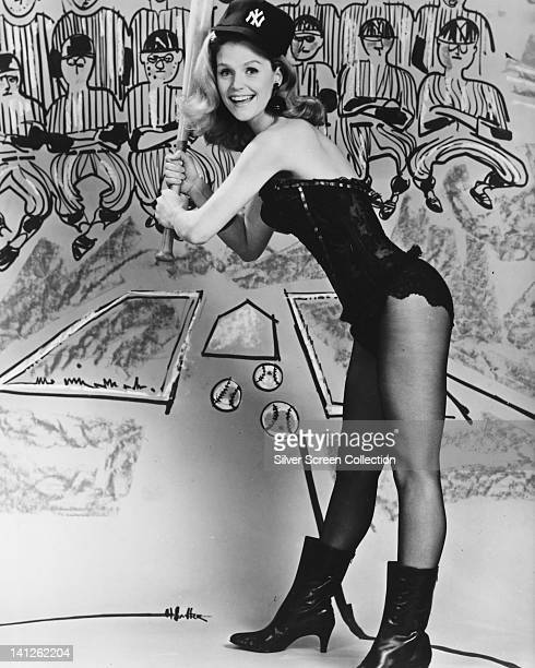 Full length portrait of Lee Remick US actress wearing a black bustier black boots and a New York Yankees baseball cap smiling as she poses with a...