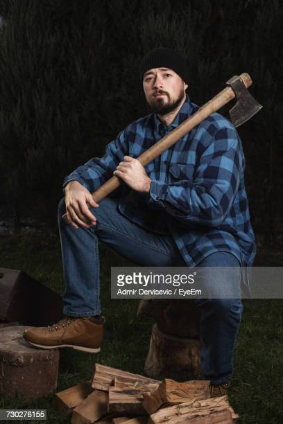 Full Length Portrait Of Lumberjack Holding Axe While Sitting On Log At Forest