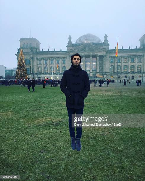 Full Length Portrait Of Man Levitating In Front Of Reichstag Building During Foggy Weather