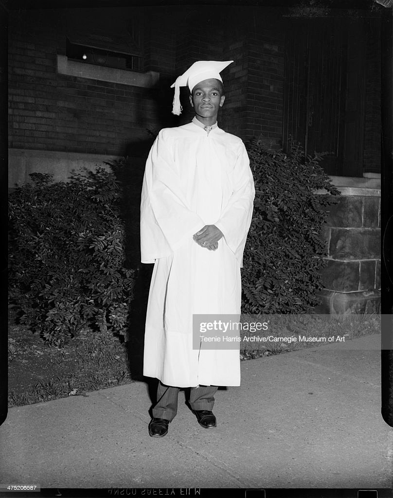 Full length portrait of man wearing light colored graduation gown and mortar board with slacks and dark shoes, standing on sidewalk of brick building for La Salle graduation, Pittsburgh, Pennsylvania, July 26, 1946.