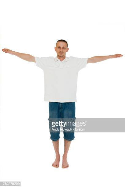 Full Length Portrait Of Man With Arms Outstretched Standing Against White Background