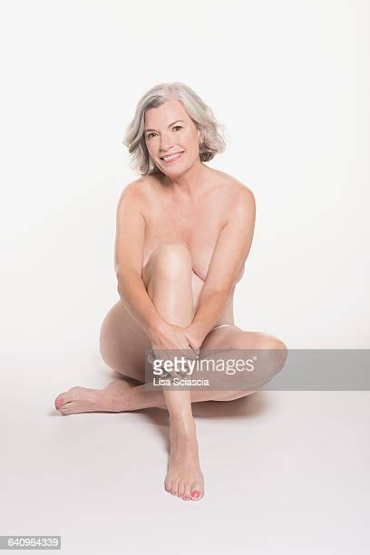Full length portrait of naked mature woman sitting against white background