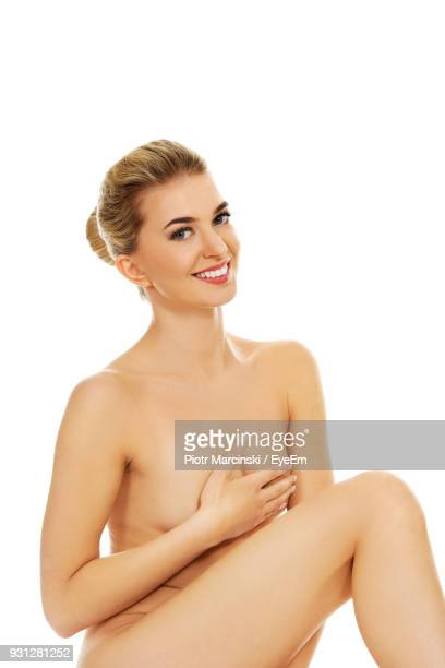 full length portrait of naked young woman sitting against white background - full frontal woman fotografías e imágenes de stock
