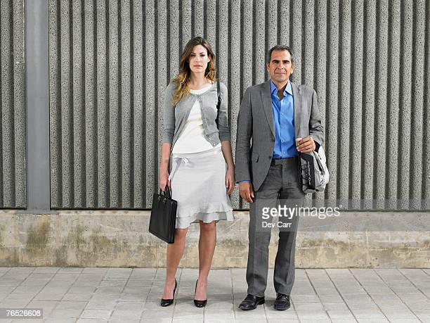 Full length portrait of older man and young woman in business suits looking into camera against textured concrete, Alicante, Spain,