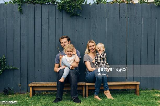 Full length portrait of parents and children sitting on seats against fence at yard