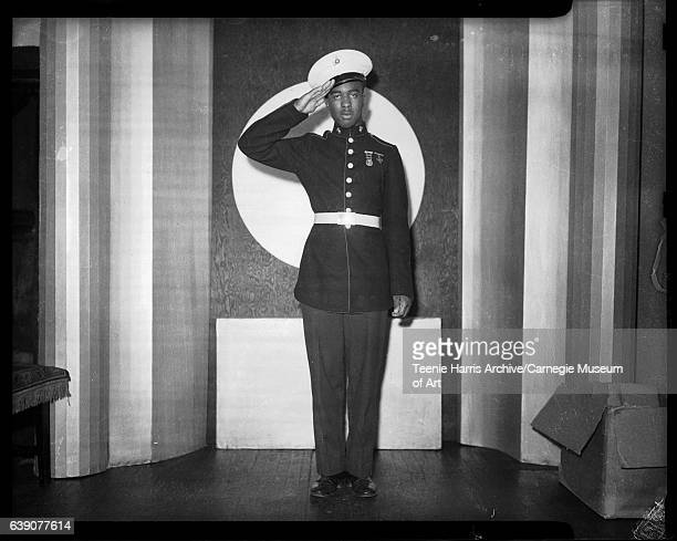 Full length portrait of saluting man wearing dark US Marine Corps uniform light colored cap and round and Maltese cross shaped medals on chest...