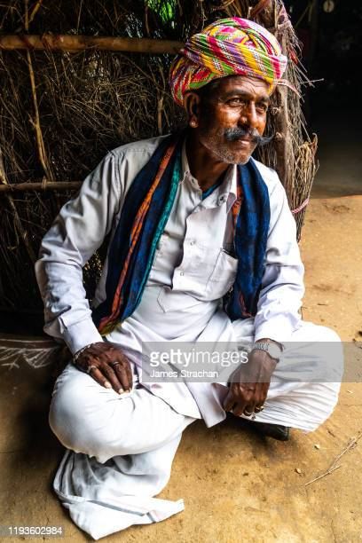 full length portrait of seated rajasthani musician looking out from his hut to see if the weather is changing for the better, pushkar fair, pushkar, rajasthan, india (model release) - james strachan stock pictures, royalty-free photos & images