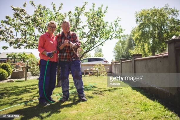 Full length portrait of senior couple holding hammer and garden hose while standing at yard