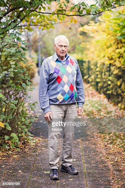 Full length portrait of senior man standing on footpath in park