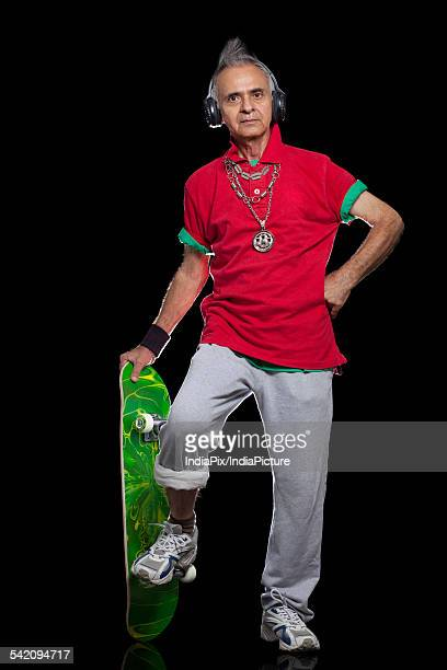 full length portrait of senior man with skateboard - funky stock pictures, royalty-free photos & images