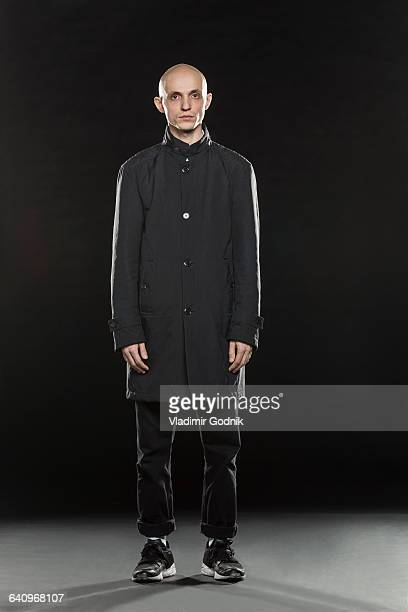 Full length portrait of serious bald man standing against black background