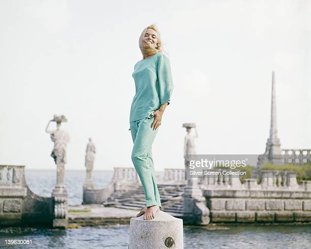 Full length portrait of Shirley Eaton British actress wearing a light blue top with matching trousers while posing with statuary at the water's edge...