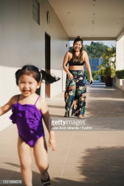 full length portrait of sisters happy in the hallway afternoon - filipino family reunion stock pictures, royalty-free photos & images