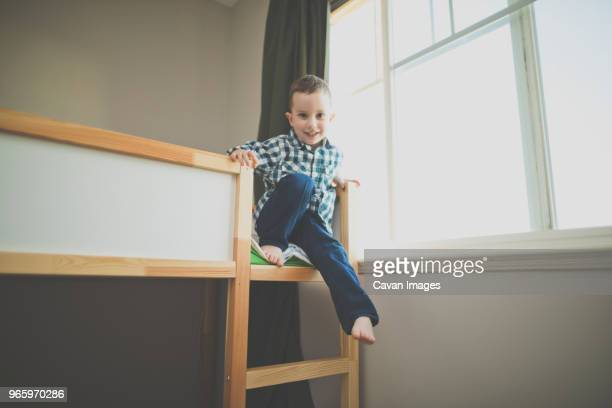 Full length portrait of smiling boy sitting on bunk bed by window at home